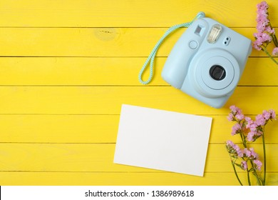 Modern polaroid camera, blank paper card, violet flowers on yellow wooden background. Top view, tender minimal flat lay style composition. Womens desk, fashion blogger, beauty technology