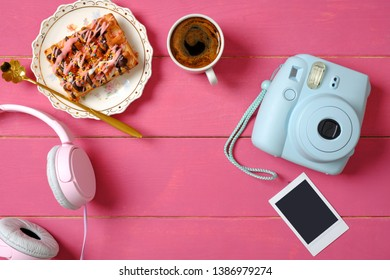 Modern polaroid camera, photo frame, coffee cup, cake, headphones on rustic pink wooden background. Top view, tender minimal flat lay style composition. Women desk, fashion blogger, beauty technology