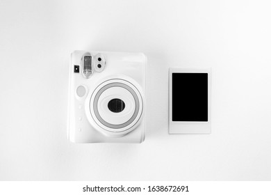 Modern polaroid camera, photo white wooden background. Top view, tender minimal flat lay style composition. fashion blogger, beauty technology