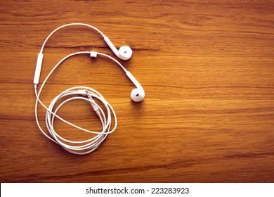 Modern portable audio earphones on wood board
