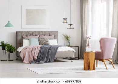 Modern poster hanging above big messy bed in a room with window