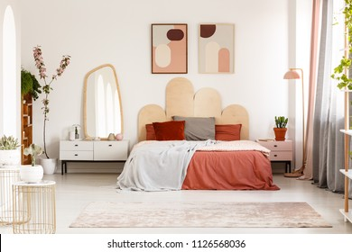 Modern posters above bed with headboard in pastel bedroom interior with mirror. Real photo