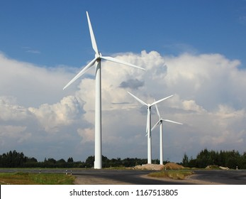 Modern power wind farm in summer against blue sky with white clouds