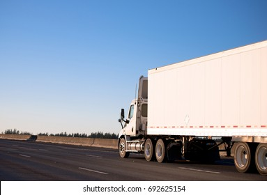 A modern powerful white big rig semi truck with a spoiler on a day cab roof, designed for local transportation of commercial cargo, delivers the goods in a dry van trailer, driving on highway I-5