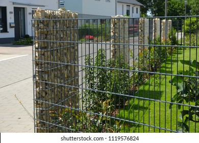 Modern Privacy Fence of Natural Rock Gabions, Wooden Boards and greened galvanized Steel Grid surrounding a residential Building (Germany)