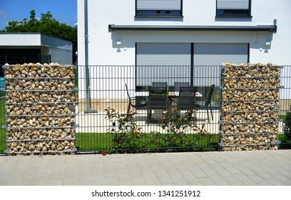 Modern Privacy Fence of Natural Rock Gabions and galvanized Steel Grid surrounding a residential Building (Germany)