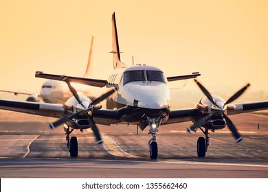 Modern propeller plane against commercial airplane on runway. Traffic at airport during sunset.