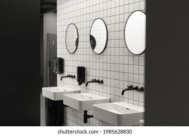 Modern public restroom minimal interior with metro style white tiles, round mirrors, black ceiling