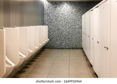 Modern public toilet for men. Clean and hygienic urinal from white tiles. Public men's toilet