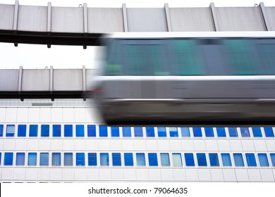 Modern public transportation system sky train hanging from elevated guide way  passes by in front of tall office building facade (with motion blur).