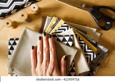 Modern quilt fabrics with sewing spools, scissors and woman hand on the wood table