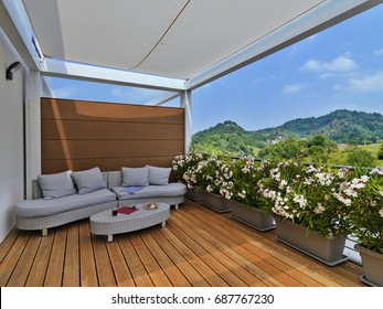 modern rattan's divan with pillows in the terrace with wooden floor and planters overlooking on the mountain