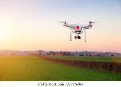 Modern RC Drone / Quadcopter with camera flying on a clear sunny sky sunset background with nice lens flare.