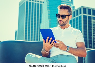 Modern Reading. Young European Man with beard, little gray hair, wearing white Polo shirt, sunglasses, sitting in business district with high buildings in New York City, reading blue tablet computer.