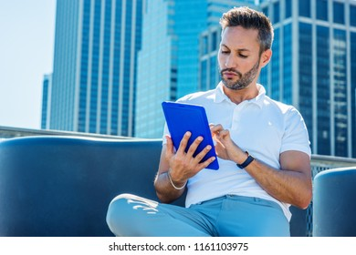 Modern Reading. Young European Man with beard, little gray hair, wearing white Polo shirt, sitting in business district with high buildings in New York City, reading, typing on blue tablet computer.