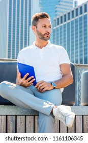 Modern Reading. Young European Man with beard, little gray hair, wearing white Polo shirt, wristwatch, sitting in business district with high buildings in New York, reading tablet computer, thinking.