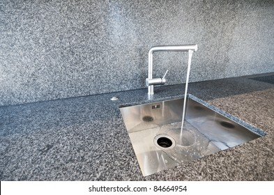 modern rectangular stainless steel kitchen sink on a granite worktop