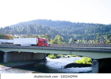 Modern red big rig semi truck with reefer semi trailer transporting commercial cargo and moving on the bridge across small mountain river in stunning natural Columbia Gorge aria with wooded hills