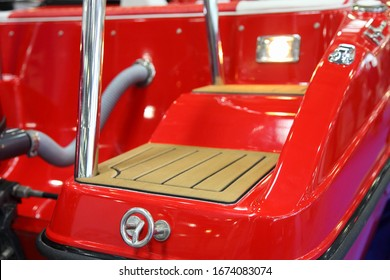 Modern red motor boat stern swimming platform with teak coating, railing and transom towing ring close up