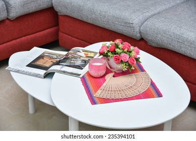 Modern Red sofa made of jute material and white center table with flowers and candle in apartment living room. Center coffee table.