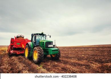 modern red tractor in the agricultural field; mechanism. Tractor plowing land. Harvester sowing wheat.