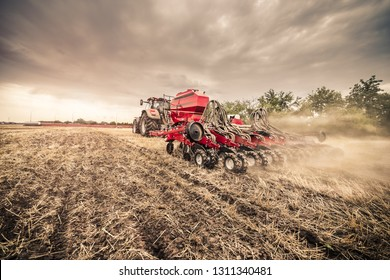 Modern red tractor with red implement seeding directly into the stubble with lot of dust around using GPS in the fertile fields of the Czech Republic.