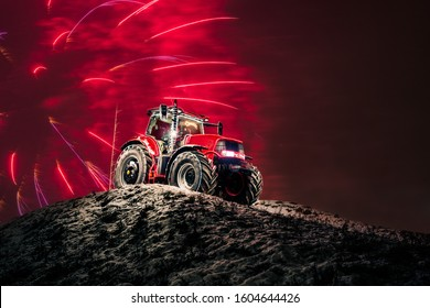 Modern red tractor standing on the top of snowy hill with red fireworks behind as a background. Agricultural machines New Year's Eve celebration.