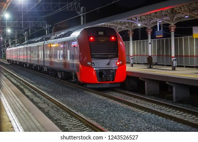 Modern red train approaching the train station