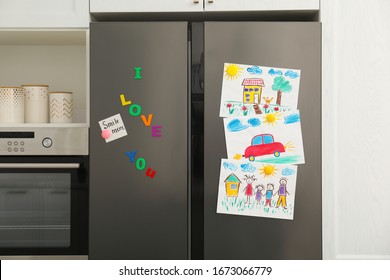 Modern refrigerator with child's drawings, note and magnets in kitchen