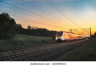 Modern regional train traveling with speed on railway tracks through nature landscape, at sunset, near Schwabisch Hall, Germany.