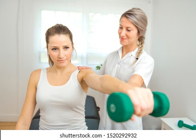 A Modern rehabilitation physiotherapist at work with client. Working on shoulder with dumbell