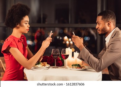 Modern Relationship. Serious African American Couple Using Mobile Phones Having Romantic Date In Restaurant.