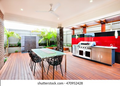 Modern and relaxing area of a luxury house, whole area covers with wooden walls, pillars and a fence, chairs are made using a beautiful carve on the wooden floor there There is a silver gas grill