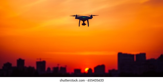 Modern Remote Control Air Drone Fly high with action camera in sunset sky. Cityscape silhouette in the background. Modern technologies. Travel, hobby, inspiration. Orange toning filter. Kiev, Ukraine