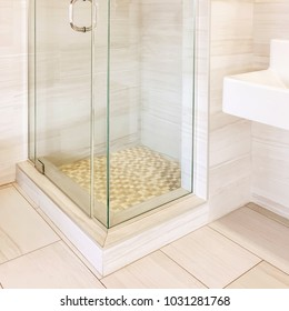 Modern renovated shower with tiled walls and floor, in beige tones.