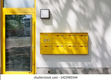 Modern residential apartment building entrance with glass door, yellow mailboxes and tree shadow on wall. New home currently under construction