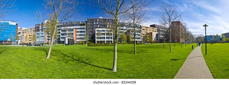 modern residential area of Amsterdam. Park with green grass and trees on the background of modern arhitecture. XXL size. Panorama