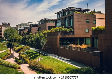 Modern residential buildings in the public green area. Apartment houses in Europe. Beautiful view of real estate homes in Milan, Italy. Business district in summer. Walking area with trees and grass.