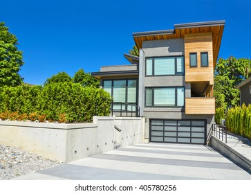 Modern residential house with emotion element in design. Detached house with wide garage for two cars, concrete driveway and landscaped terrace in front on blue sky background.