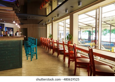 Modern restaurant or cafe interior. Public place interior design, bright red and blue wooden chairs, large windows and bar. Morning light, nobody indoors.