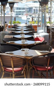 Modern restaurant with the covered tables, knives and forks, furniture, table napkins. Vertical photo