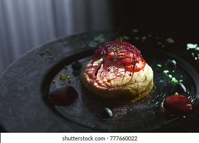 Modern restaurant dessert closeup. Lemon cheesecake with berry spheres and caramel decoration served on black textured plate with almond flakes. Exclusive meals and haute cuisine concept