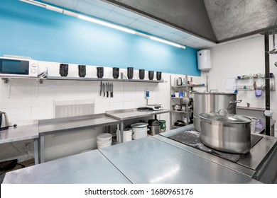 Modern restaurant kitchen with stainless steel kitchenware and equipment. Cooking with preparation tables, pans, pots, stoves.