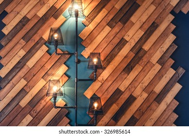 Modern restaurant with rustic decorative elements. Interior design details with lamps and bulb lights. Wooden wall decoration with vintage looking lights