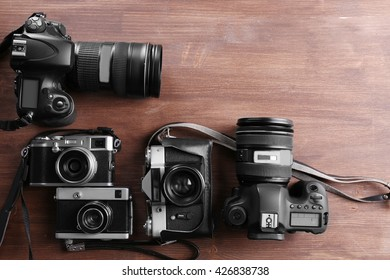 Modern and retro cameras on wooden background