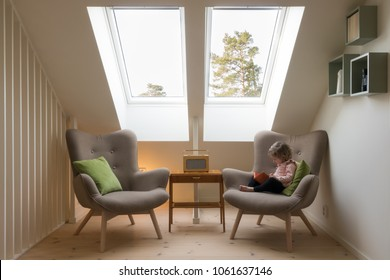 Modern retro design in a attic / loft. Small vintage table with a radio on and two reading chairs under two skylights with a little child reading a book.