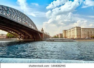 Modern river ship on the background of the bridge in the city. The ship sails on the city river sailing under the beautiful bridges in the city on the river. Picturesque modern urban architecture
