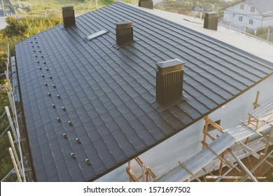 Modern roof made of metal. dark gray roof of an industrial building made of metal. Corrugated metal roof and metal roofing.