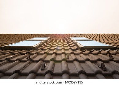 Modern Roof Skylight Window on brown House Clay Ceramic Tiles Roof. Roofing Construction.