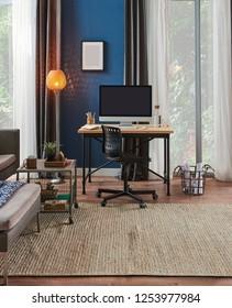 Modern room, blue wall, desktop oın the wooden desk and grey sofa decoration room.